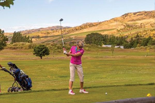 Woman Swinging Golf Club at Golf Course
