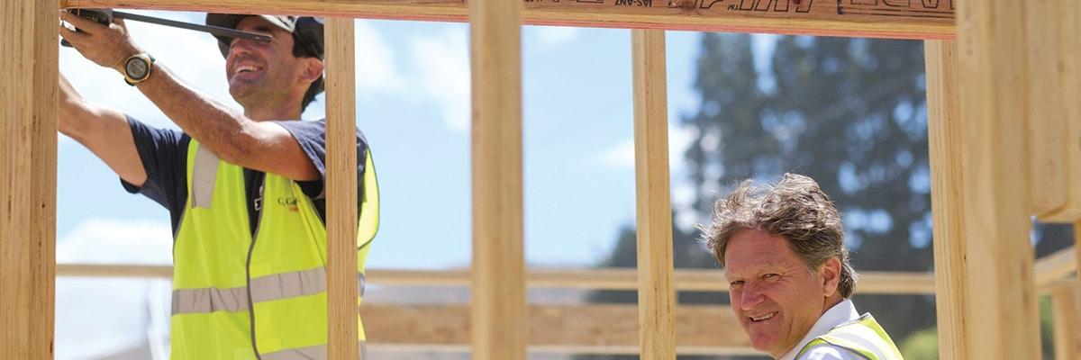 Two Men Measuring Building Framework
